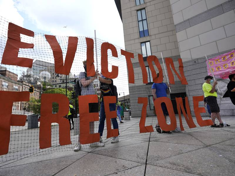In this June 9, 2021, photo, people hold a sign during a rally in Boston protesting housing...