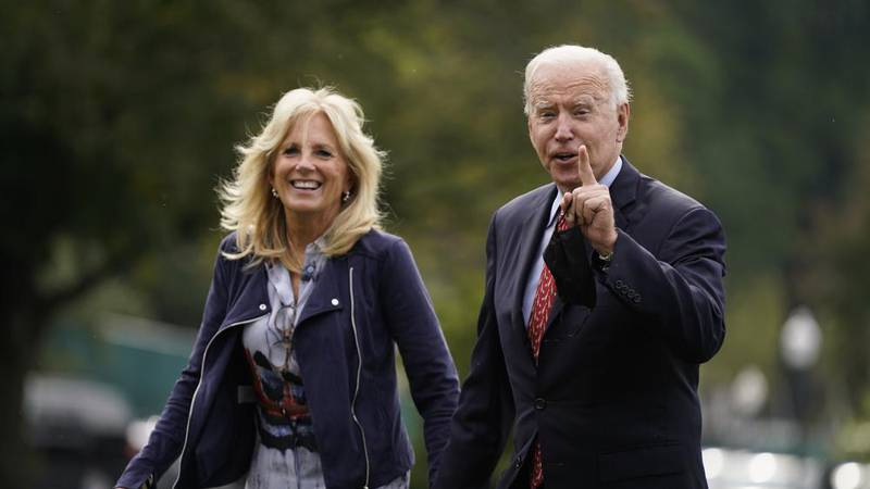 President Joe Biden and first lady Jill Biden arrive on the South Lawn of the White House after...