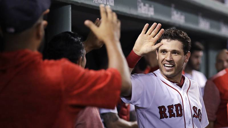 Boston Red Sox's Ian Kinsler smiles as he is congratulated after scoring on a wild pitch by...